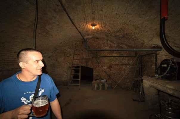 """Fryštátský ležák 11° a pivovarské sklepy. Ve sklepeních funguje zařízení, kterým zahřívají pivo na správnou teplotu. Ano - opravdu zahřívají, ze 4°C na těch správných 6-8°C. Nahoře u stropu vedou """"pivní trubky""""."""