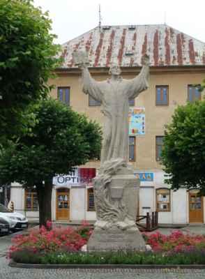 """Jsme na Husově náměstí, a tak nesmí chybět socha Mistra Jana Husa. Bohužel, bez reklamy na tu nejlepší zmrzlinu se mi ji vyfotit nepovedlo. Sochu zhotovil táborský sochař Rudolf Kabeš (1885 – 1974) z umělého kamene. Mistr Jan Hus drží v pravé ruce otevřenou knihu s nápisem """"Pravda vítězí"""" a na podstavci je nápis """"Milujte se vespolek, pravdy každému přejte"""". Socha byla slavnostně odhalena v květnu 1926 za veliké účasti občanů."""