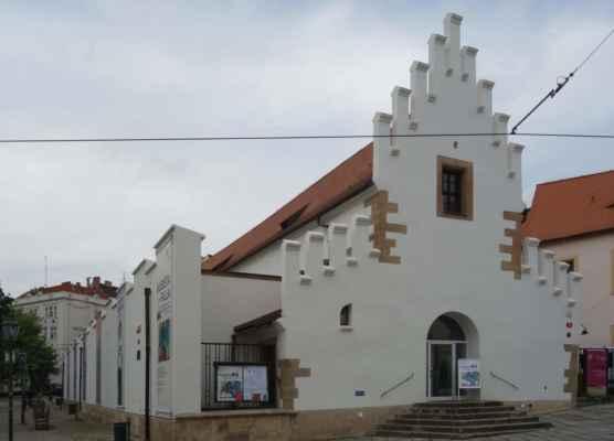 A jsme u Masných krámů - budova masné tržnice s typickým štíhlým cimbuřím byla postavena v roce 1392. Z doby gotiky má budova trojlodní půdorys. V roce 1856 byla vyvýšena její středová část. Budova sloužila jako tržnice do 2. světové války, potom zde bylo skladiště. V roce 1962 měla být zbourána, ale o tři roky později bylo rozhodnuto o využití budovy jako výstavní síně Západočeské galerie. O deset let později od vydání demoličního výměru zde byla otevřena výstavní síň, která se zde nachází do dnešní doby.